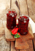 Jars of strawberry jam with berries on wooden background — Stock Photo