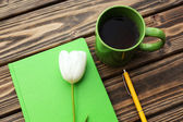 Notebook with cup of tea and white tulip on wooden background — Stockfoto