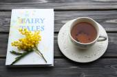 Fairy Tales book with cup of tea and sprig of mimosa on wooden background — Stock Photo