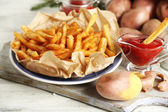 Tasty french fries on cutting board, on wooden table background — 图库照片