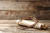 Crown of thorns and scroll on old wooden background — Stock Photo