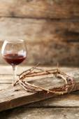 Crown of thorns and glass of wine on old wooden background — Stock Photo