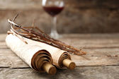 Crown of thorns, scroll and glass of wine on old wooden background — Stock Photo