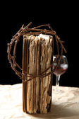 Crown of thorns and bible on black background — Stock Photo