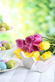 Easter decoration, eggs and tulips on table on natural background — Stock Photo