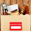 Box of unwanted stuff ready for a garage sale on wooden background — Stock Photo #68728193