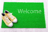 Sneakers and green carpet on floor — Stock Photo