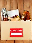 Box of unwanted stuff ready for a garage sale on wooden background — Stock Photo