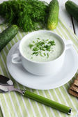Cucumber soup in bowl on color wooden table background — Stock Photo