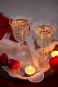 Champagne glasses and rose petals for celebrating Valentines Day on dark background — Stock Photo