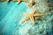 Sea stars on sea salt on wooden background — Stock Photo