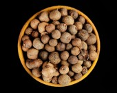 Allspice in wooden bowl, isolated on black — Stock Photo