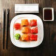 Sushi rolls on plate, soy sauce and chopsticks on wooden background — Zdjęcie stockowe #68730471