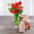 Beautiful roses in vase on table on light background — Stock Photo #68731055