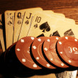 Playing cards with chips on wooden table, closeup — Stock Photo #68734441