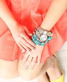 Stylish bracelets and clock on female hand close-up — Stock Photo