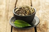 Green tea with leaf in cup on old wooden table — Stockfoto
