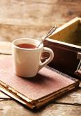 Old wooden suitcase with old books and tea cup on wooden background — Foto de Stock