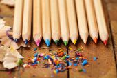 Wooden colorful pencils with sharpening shavings, on wooden table — Stock Photo