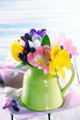 Beautiful spring flowers on wooden table on blue background — Stock Photo