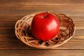 Apple in wicker basket on wooden background — Stock Photo