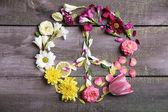 Peace symbol of beautiful flowers, on wooden table  — Zdjęcie stockowe