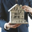 Model of house made of money in male hands isolated on white background — Stock Photo #68754809