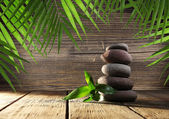 Spa stones and bamboo on wooden background — Stock Photo