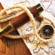 Marine still life spyglass, compass, rope and world map on wooden background — Stock Photo #68792425