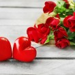 Red roses wrapped in paper with hearts on wooden table background — Stock Photo #68793495