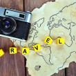 Retro camera on world map with word Travel on wooden table background — Stock Photo #68793585