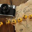 Retro camera on world map with word Travel on wooden table background — Stock Photo #68793595