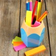 Colorful pencils in holder with sticky notes on wooden planks background — Stock Photo #68794643