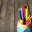 Colorful pencils in holder with sticky notes on wooden planks background — Stock Photo #68794649