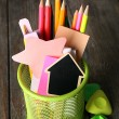 Colorful pencils with paper notes in metal stand on wooden table background — Stock Photo #68794707