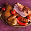 Assortment of smoked meat on metal tray on color wooden table background — Stock Photo #68795533