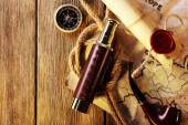 Marine still life spyglass, rope, pipe and world map on wooden background — Stock Photo