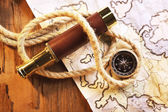 Marine still life spyglass, compass, rope and world map on wooden background — Stock Photo