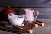 Black tea with milk in cups and teapot with lump sugar on color wooden planks background — Stock Photo