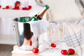 Champagne bottle in bucket,  glasses and rose petals for celebrating Valentines Day — Stock Photo