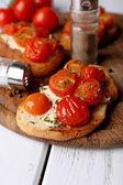 Ломтики белого поджаренного хлеба с маслом и консервированные помидоры на фоне цвета деревянных планок — Стоковое фото