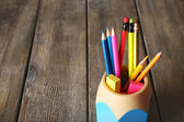 Colorful pencils in holder with sticky notes on wooden planks background — Stock Photo