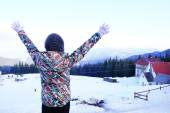 Woman in warm clothing turned back raising her hands up over Carpathian Mountains in wintertime — Stock Photo
