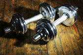 Dumbbells on wooden floor, on dark background — Foto de Stock