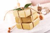 Stack of tied spa soap on wooden table, closeup — Stock Photo
