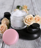 Cosmetic cream with flowers and spa stones on wooden background — Stock Photo