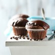 Tasty homemade chocolate muffins and cup of coffee on wooden table, on light background — Stock Photo #68846123