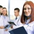 Beautiful young doctor with team in conference room — Stock Photo #68846493