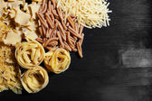 Different types of pasta on wooden table background — Stock Photo