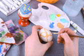 Painting Easter eggs by female hands on colorful tablecloth background — Stockfoto